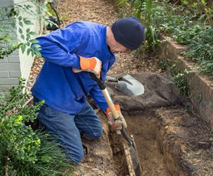Man Inspects Pipe and Digs Trench